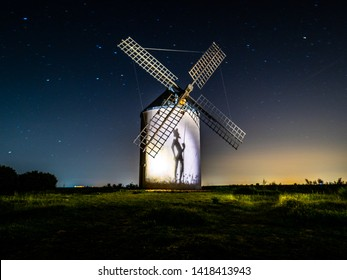 Night photograph of a windmill with the silhouette of don Xijote making a shadow.