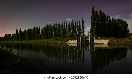 Night photography wehere a river can be seen. The poplar line is reflected on the water. Some stars and clouds in the sky can be appreciated. On the right, there is a floodgate. Blue hour. Valley, Pat