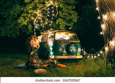 Night picnic of a young couple near a green bus on a background of yellow garlands in the forest