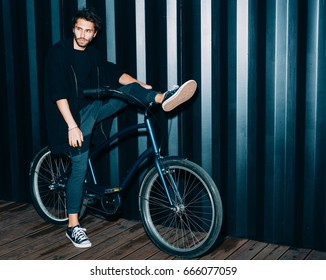 Night portrait with a flash of a young man in a fashionable black outfit, sneakers put one foot on the wheel of a vintage bicycle.