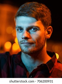 Night portrait of a hipster man. He is dressed in a plaid shirt. Night city lights in the background. Cold light