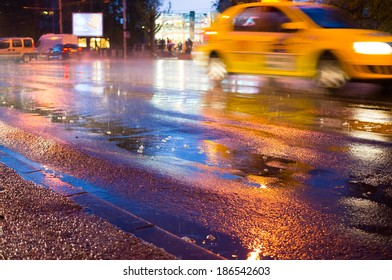 Night rain in the city with rain drops and taxi