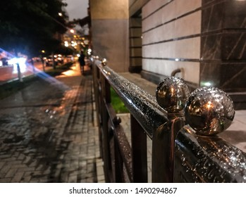 Night. Rain drops on a metal balloon - decoration fence on the background of the wet streets on blurred background of the sidewalk from passers-by and road with the bright lights of the oncoming car