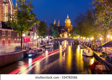 Night red-light district De Wallen, canal, Basilica of Saint Nicholas and bridge, Amsterdam, Holland, Netherlands. Long exposure. Used toning