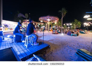 Night resort beach full of tourists.  Petformance of musical band on wooden stage. Fresh tropical evening