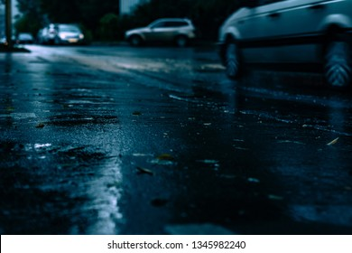 Night road blurred. Rain drops rippling in a puddle on a dark, rainy day, close up with soft selective focus . Water splashes, spills on roadway