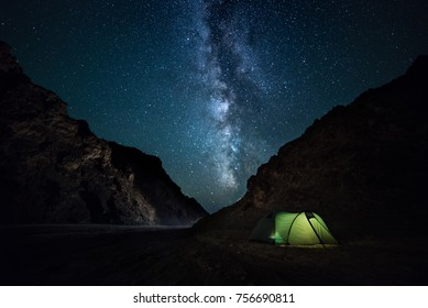 night rocky ravine. starry sky with bright milky way. an illuminated tent