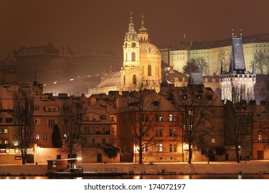 Night romantic snowy Prague St. Nicholas' Cathedral above River Vltava, Czech republic
