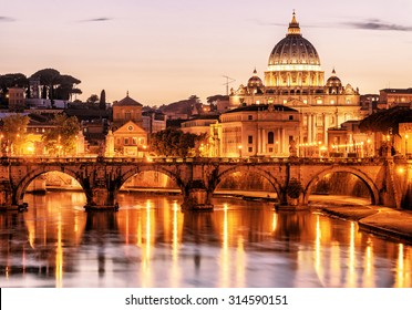 Night romantic view of San Pietro or St Peter basilica, Rome, Italy. Beautiful panorama of Rome at dusk. Scenery of Rome with Tiber River in evening. Illumination of Rome in twilight. Roma postcard.