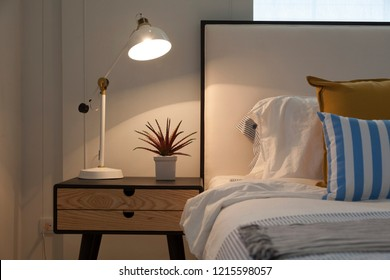 Night scene of bedroom setting including bedside table ,white lamp and plant pot on it.