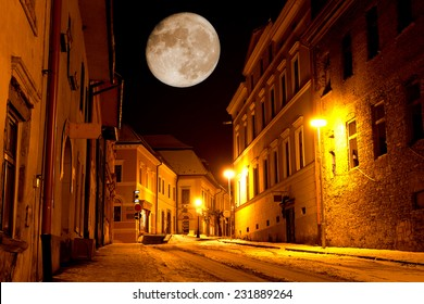 Night scene with big moon in old city