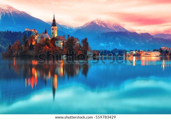 Ночная сцена озера Блед в Словении, известное и популярное место для романтической влюбленной пары. Художественный тонизирующий пейзаж. Фантазия пост-обработки.