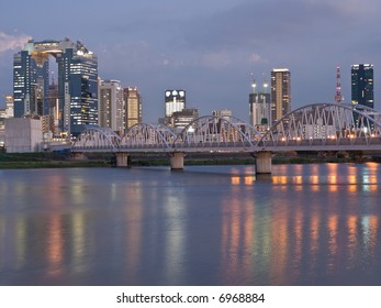 Night scene of bridge crossing Yodo river with reflections in the foreground and Osaka city skyline in the background. These highrises are part of Umeda which is the central business district in Osaka