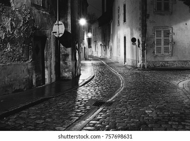A night scene captures an empty street in the city of Beaune in France where the wet cobblestones are bright with reflected light from the street lights. (Scanned from black and white film.)