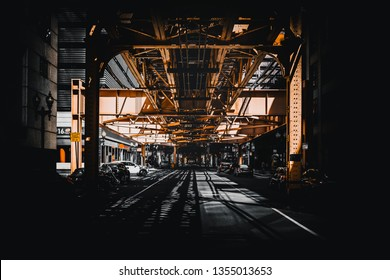 Night scene in Chicago, USA with a view under receding steel girders to a car in the street in front of commercial buildings