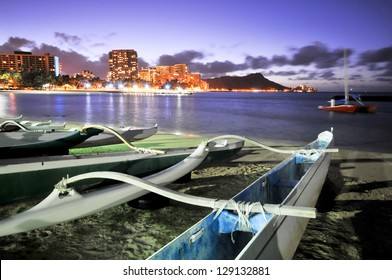 Night scene of a group of outrigger canoes on the beach with Diamond Head
