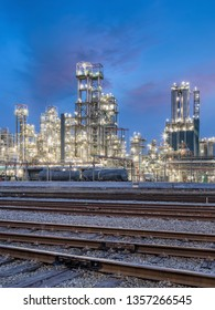 Night scene with illuminated petrochemical production plant with train tracks in front, Antwerp, Belgium.