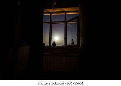 Night scene of moon seen through the window from dark room. Moonlight inside dark room