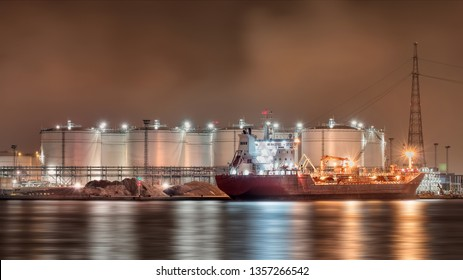 Night scene with moored tanker at embankment of Illuminated petrochemical production plant, Port of Antwerp, Belgium.