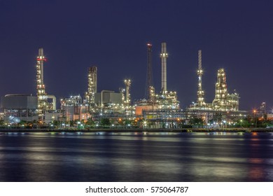 Night scene of oil refinery plant of Petrochemistry industry in twilight time and reflection in near river in Bangkok, Thailand.