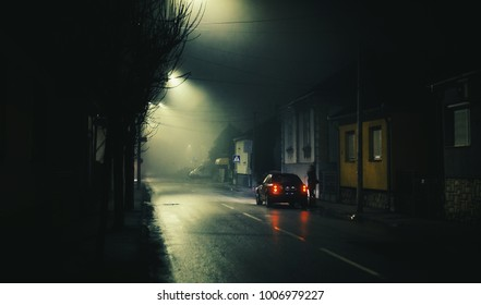Night scene on foggy street of a small town, lonely woman and one car.
