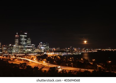 Night scene of Perth city center with a rising full moon