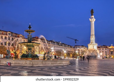 Night scene of Rossio Square, Lisbon, Portugal with one of its decorative fountains and the Column of Pedro IV.