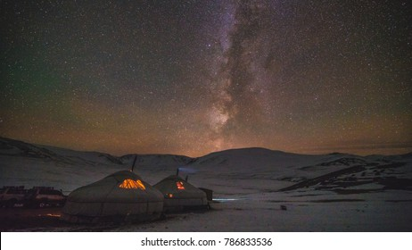 Night scene of the twinkling stars of the Milky Way over Mongolian yurts with glowing lights in a rugged snowy mountain landscape