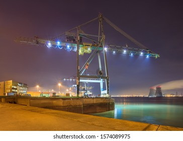 Night scene with view on with illuminated container terminal and massive crane, Port of Antwerp, Belgium.