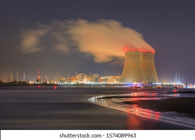 Night scene with view on riverbank with nuclear reactor Doel, Port of Antwerp, Belgium.