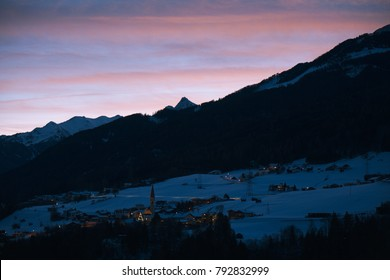 Night scenery of the Austrian village in Pitztal valley. City lights are shining like tiny stars on the background of black forest on mountains