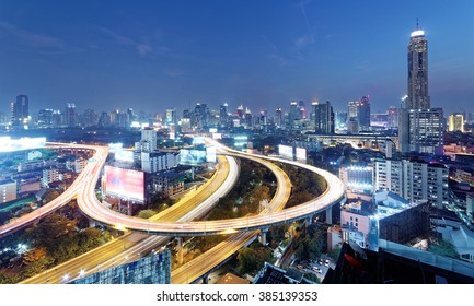 Night scenery of Bangkok with skyscrapers in background and busy traffic trails on elevated expressways & circular interchanges ~ Bangkok at rush hour with heavy traffic on intertwined highway bridges