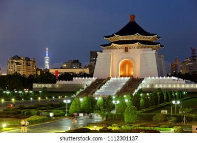 Night scenery of Chiang Kai-Shek Memorial Hall by Liberty Square, a landmark and tourist attraction in Taipei, Taiwan, with the famous 101 Tower standing among high-rise buildings in the background