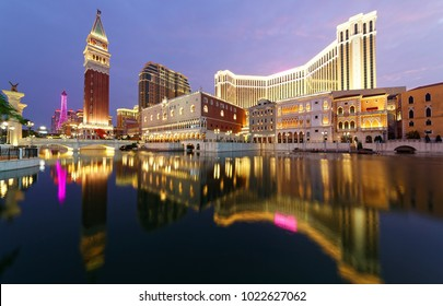 Night scenery of the extravagant exterior of the Venetian Macao, a luxury hotel & casino resort in Macau, China, with reflections of beautiful buildings and colorful neon lights in the water of a pool