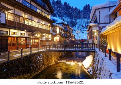 Night scenery of Ginzan Onsen, a famous hot spring town in Obanazawa, Yamagata, Japan, with bridges over a stream flanked by old buildings and tourist enjoying the view on a cold snowy winter evening