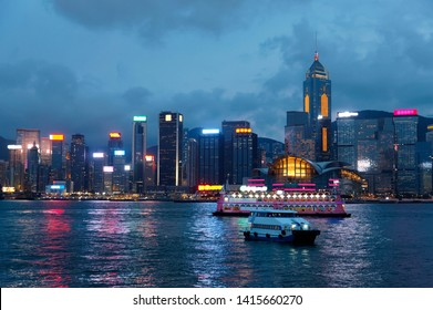 Night scenery of Hong Kong by Victoria Harbour, with Convention & Exhibition Centre (HKCEC) among crowded skyscrapers, brilliant city lights reflected in the water and tourist boats cruising at dusk