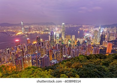 Night scenery of Hong Kong viewed from top of Victoria Peak with city skyline of crowded skyscrapers by the harbour and Kowloon area across seaport ~ Beautiful cityscape of Hong Kong in pink twilight