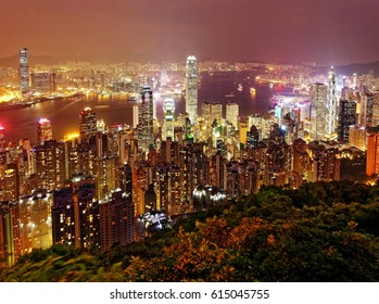 Night scenery of Hong Kong viewed from top of Victoria Peak with city skyline of crowded skyscrapers by Victoria Harbour & Kowloon area across seaport ~ Beautiful cityscape of Hongkong at misty dusk