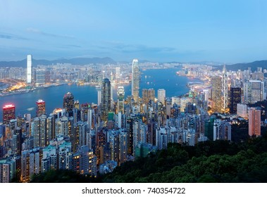 Night scenery of Hong Kong viewed from top of Victoria Peak with a beautiful skyline of crowded skyscrapers by Victoria Harbour, Kowloon area across seaport & city lights glistening in blue twilight
