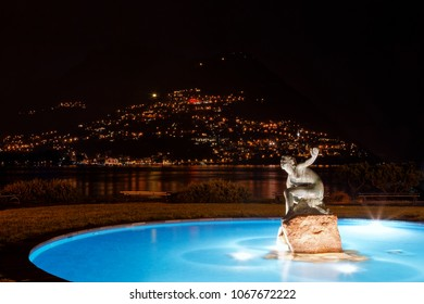 Night scenery of an illuminated fountain by Lake Lugano with a beautiful statue in the middle of blue water and lights from houses sprawling on Monte Bre in background in Paradiso, Lugano, Switzerland
