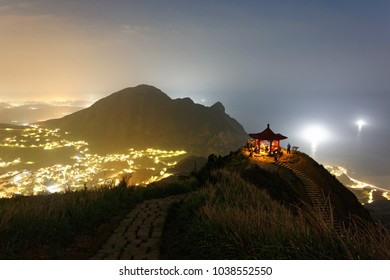 Night scenery of Jiufen, a famous tourist town near Keelung on Northeast Coast of Taiwan, with view of an oriental Gazebo perched on a mountaintop & lights from the village sprawling at the foothill