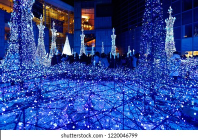Night scenery of Winter Illumination Display in a pedestrian square in Caretta Shiodome Shopping Area, Tokyo, Japan, with decorated Christmas trees and dazzling lights in a romantic dreamy atmosphere