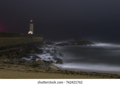 night seascape with a lonely lighthouse on the ocean shore