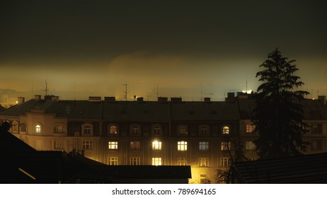 night setting upon old  buildings on a foggy day
