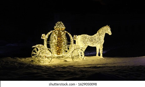 Night shooting: a fabulous, magical, festive glowing street decoration on the background of snow, night sky. Light sculpture,figure of Cinderella's carriage and horse made of garlands and yellow balls