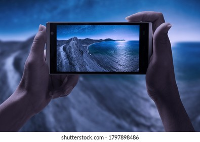 Night shooting on a smartphone. Girl take a picture of Milky Way above the Crimea sea bay at night.