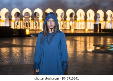Night shot of beautiful young woman wearing traditional Arab clothes at Mosque Abu Dhabi, United Arab Emirates.
