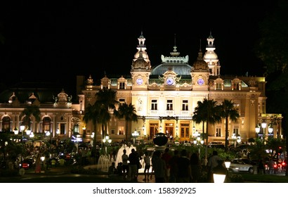 Night shot of a floodlit Monte Carlo Casino with fountains and people in silhouette. Shows a bustling atmosphere.