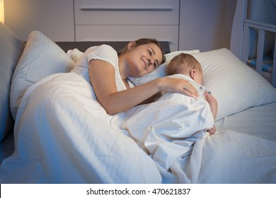 Night shot of happy smiling mother lying on bed with her beautiful baby