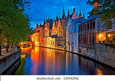 Night shot of historic medieval buildings along a canal in Bruges, Belgium
